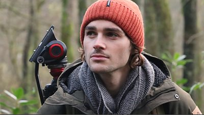Jack is wearing an orange woolly hat, grey scarf and green coat, he is standing in front of a camera tripod