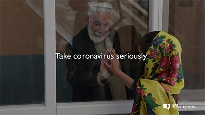 An actor playing a grandfather in Afghanistan touches his granddaughters hand against a pane of glass in a window - to demonstrate how to stay safe from COVID-19.