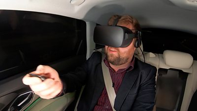 Dave Lee in the back of an Audi, wearing VR