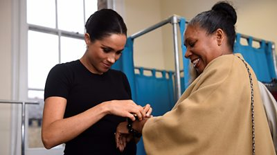 The Duchess of Sussex ties a bracelet round the wrist of a woman at Smart Works