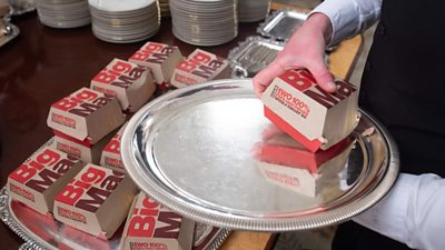 Pile of Big mac burgers being placed on silver tray