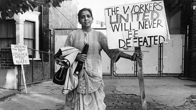 Female south asian striker holding placard