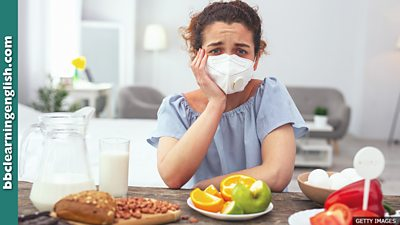 A woman wearing a breathing filter sitting in front of lots of food that people are commonly allergic to