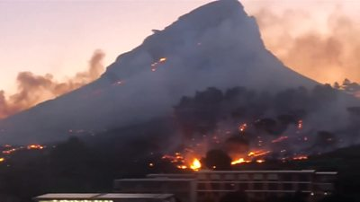 Nearly 100 firefighters have been fighting a wildfire in Cape Town's Lion's Head mountain