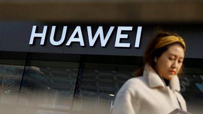 Woman walks past Huawei shop