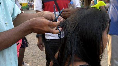 Luis Fernando cuts a woman's hair
