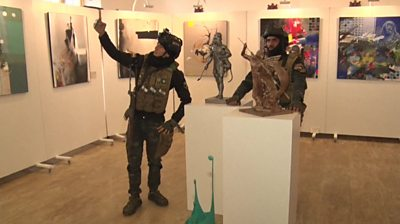 Two Iraqi soldiers, including one taking a selfie next to a sculpture