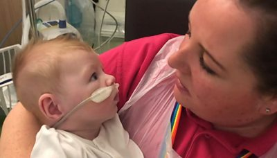 Woman cuddling a baby in hospital