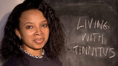 "Natalie Lue stands in front of a blackboard reading ""Living with tinnitus"""
