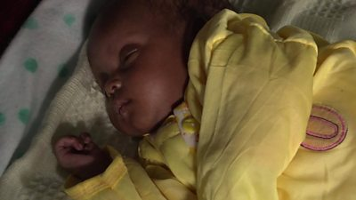 Baby girl under yellow duvet