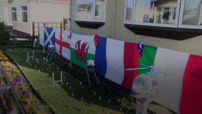 A mini rugby pitch with flags and miniature players