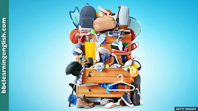 A very cluttered chest of drawers that's overflowing with a range of objects