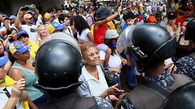 A woman talks to a line of Bolivarian National Police officers, PNB, during a protest against Nicolas Maduro in Caracas