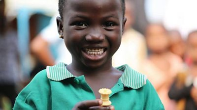 Young Nigerian girl holds chess piece and smiles wearing green shirt
