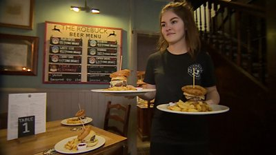 Young woman carrying plates of burgers