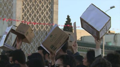 Protesters holding up cardboard boxes.