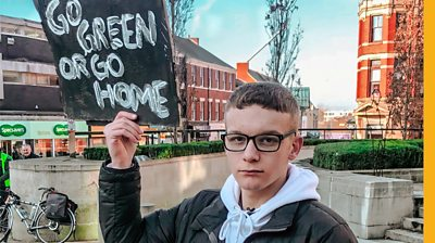 "Izaak Cowell holding a sign ""Go Green or Go Home"" while protesting in Preston"