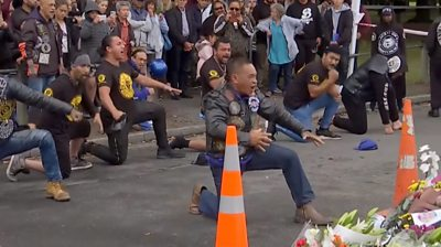 Bikers performing a haka dance next to flowers