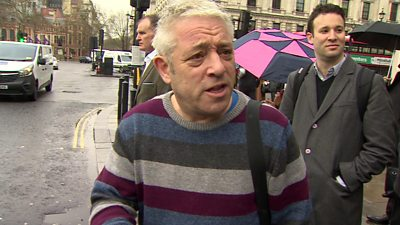 John Bercow in stripey jumper walking along street