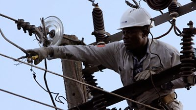 An engineer dressed in protective gear works on an electricity pylon