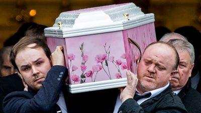 Two men carry Lauren Bullock's coffin