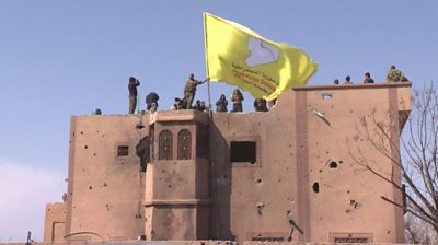 Kurdish-led fighters in eastern Syria raise a yellow flag as they celebrate the defeat of IS