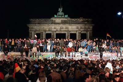 Archive image of Berlin Wall with people sat on it