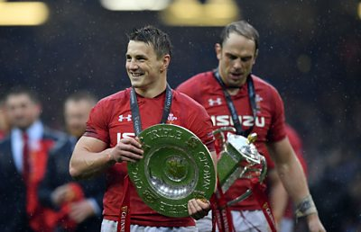 Wales centre Jonathan Davies celebrates the 2019 Grand Slam carrying the Triple Crown trophy