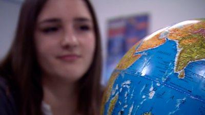 A school girl looks at a globe