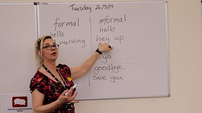 The teacher pointing at 'hey up' on a whiteboard.