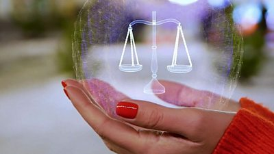 A virtual scales of justice in a woman's hand