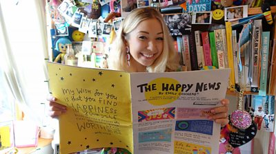 Emily Coxhead holding the Happy Newspaper