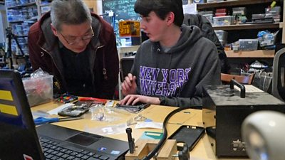 Two men repairing a mobile phone