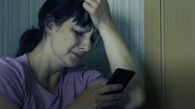 Woman looking distressed with mobile phone