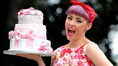 Georgie Rowe holding a cake
