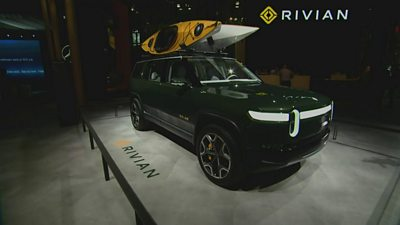 Green Rivian electric truck on show stand