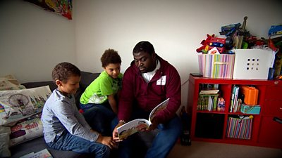 Suhmayah reading to his two chilren