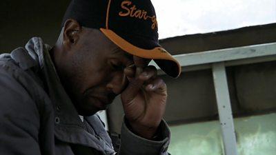 A man in a cap rubbing his eyes