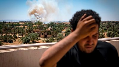 A Libyan fighter turns away as smoke rises in the distance
