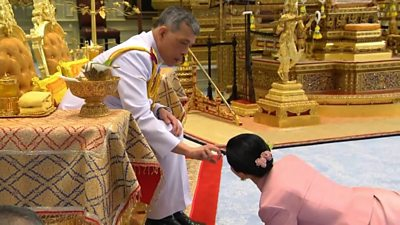 The king is seen pouring sacred water on the head of Queen Suthida