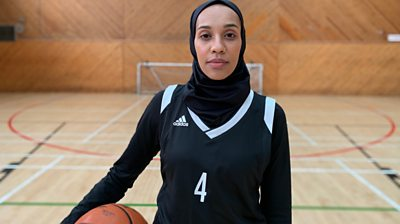 A woman in a hijab holding a basketball