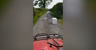 A large amount of fly-tipped items on a country road