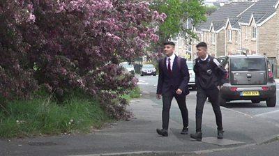 Two people walking in Bradford