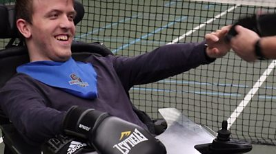 A man in a wheelchair putting on a boxing glove