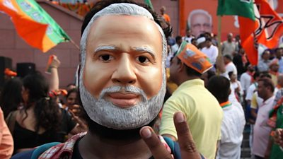 A BJP supporter wearing a Modi mask