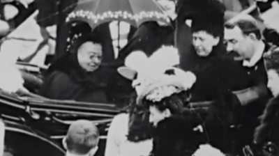 Queen Victoria in a carriage, surrounded by crowds