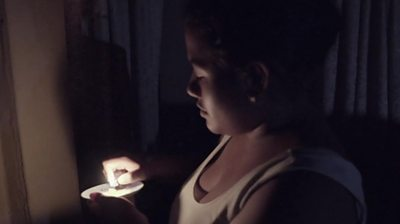 A woman holds a candle during a blackout in Venezuela