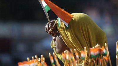 An Indian street vendor sells national flags