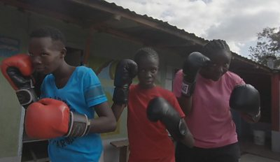 Girls line up wearing boxing gloves