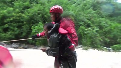 A rescuer helps a man navigate the floodwaters
